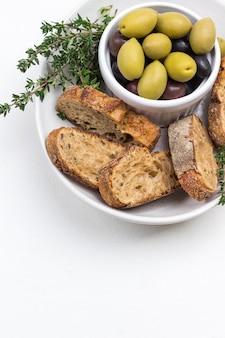 Azeitonas e fatias de pão em uma tigela de cerâmica. copie o espaço. vista do topo