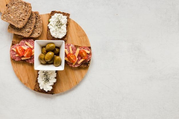 Azeitonas e sanduíches na tábua com espaço de cópia