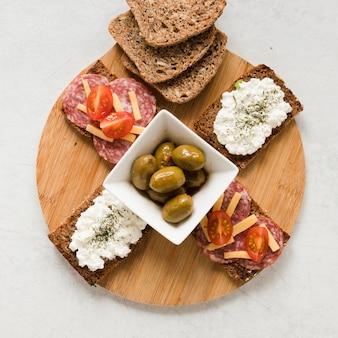 Azeitonas e sanduíches na tábua