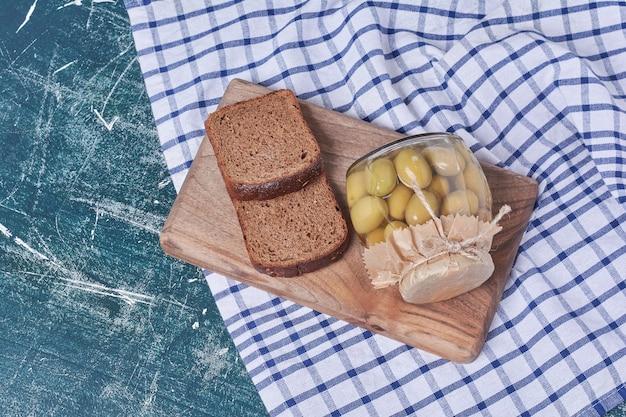 Azeitonas em conserva em frasco de vidro com fatias de pão preto no azul.