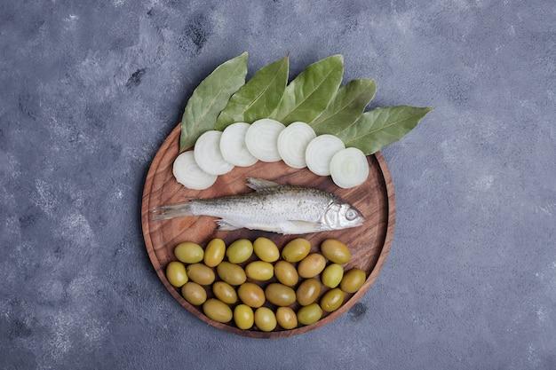 Azeitonas em conserva, folhas, peixe e anéis de cebola na placa de madeira.