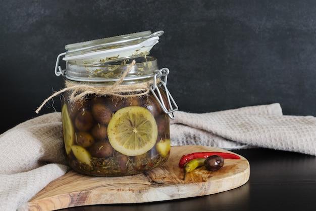 Azeitonas em uma jarra de vidro em óleo com fatias de limão em fundo escuro.