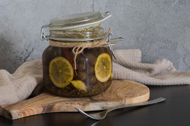 Azeitonas em uma jarra de vidro em óleo com rodelas de limão em fundo cinza.