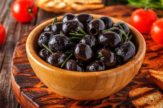 Azeitonas frescas com baguete torrada em uma tábua de madeira