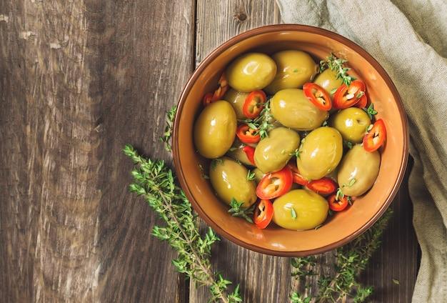 Azeitonas frescas com pimenta e tomilho em uma tigela com fundo de madeira rústico