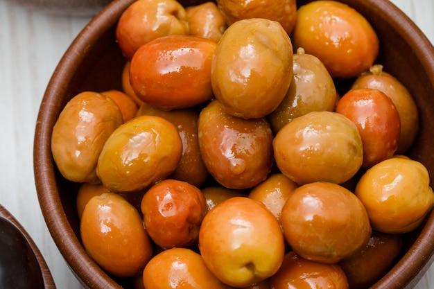 Azeitonas frescas em uma tigela de barro em madeira branca. fechar-se.