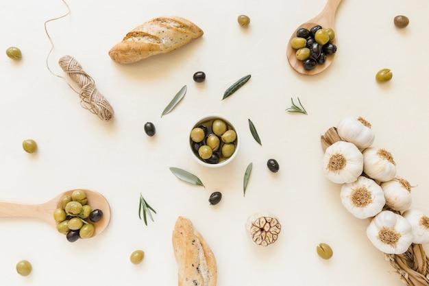 Azeitonas no prato e colheres com alho e pão
