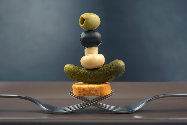 Azeitonas, pepino em conserva, pão, cogumelos em um garfo close-up em uma mesa escura