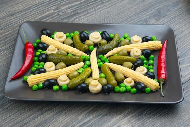 Azeitonas, pepino em conserva, pimenta, cogumelos e milho em uma salada em um prato. alimentos e vegetais. dieta e perda de peso