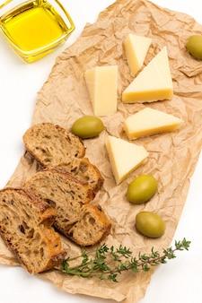 Azeitonas, queijo parmesão e raminhos de tomilho no papel. vista do topo.