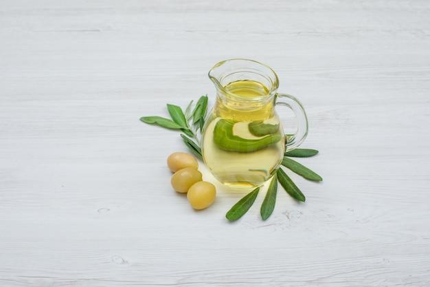 Azeitonas verdes e azeite de oliva em uma jarra de vidro com folhas de oliveira vista lateral na prancha de madeira branca