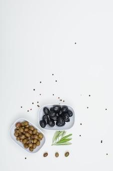 Azeitonas verdes e pretas em um prato branco com especiarias e folhas de oliveira vista superior em branco
