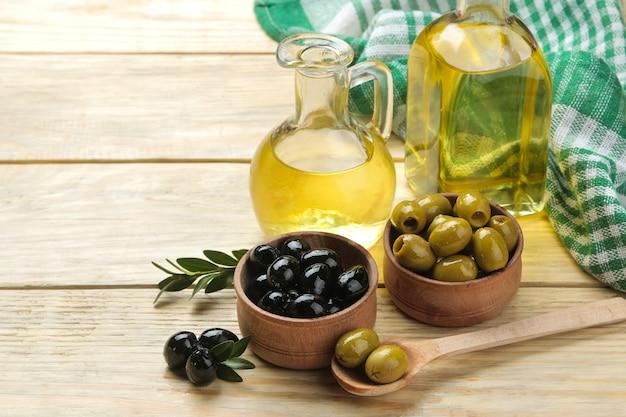 Azeitonas verdes e pretas em uma tigela de madeira com folhas e azeite de oliva em uma mesa de madeira natural