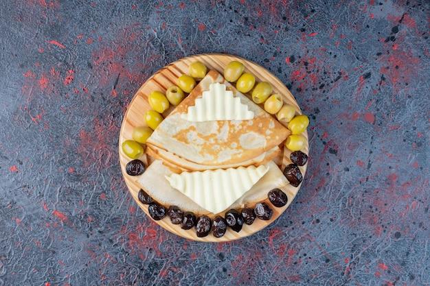 Azeitonas verdes e pretas marinadas com rodelas de queijo branco.