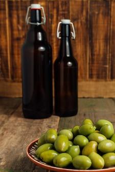 Azeitonas verdes em uma tigela marrom na garrafa de óleo perto de madeira.