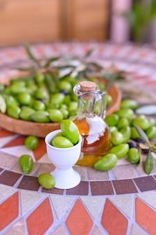 Azeitonas verdes frescas com galhos e folhas. colheita sazonal na itália. garrafa de azeite e frutas sobre uma mesa de pedra.