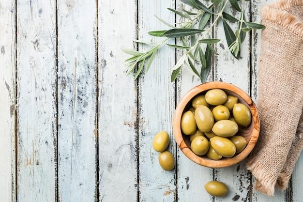 Azeitonas verdes frescas em uma tigela e ramo de oliveira em madeira rústica
