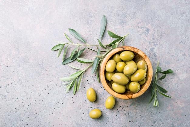 Azeitonas verdes frescas em uma tigela e ramo de oliveira na pedra rústica