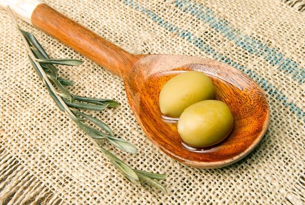Azeitonas verdes frescas na colher e óleo