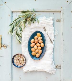 Azeitonas verdes grandes em placa de cerâmica rústica com galho de árvore e especiarias na toalha de cozinha, mesa de luz azul