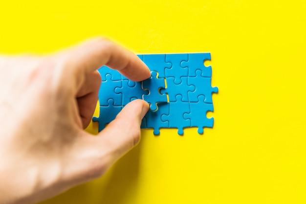 Azul quebra-cabeça na mão em fundo amarelo. mão segurando a peça do quebra-cabeça.