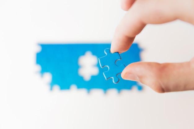 Azul quebra-cabeça na mão. mão segurando a peça do quebra-cabeça. peça de conexão, conexão de negócios, educação, sociedade e trabalho em equipe
