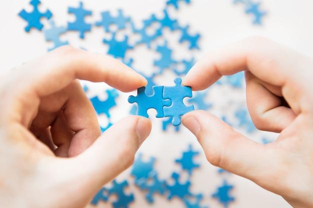 Azul quebra-cabeça na mão. mão segurando a peça do quebra-cabeça sobre fundo branco. peça de conexão, conexão de negócios, educação, sociedade e trabalho em equipe