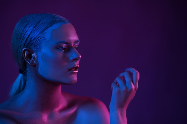 Azul roxo retrato de modelo nu sexy na luz de neon em fundo escuro