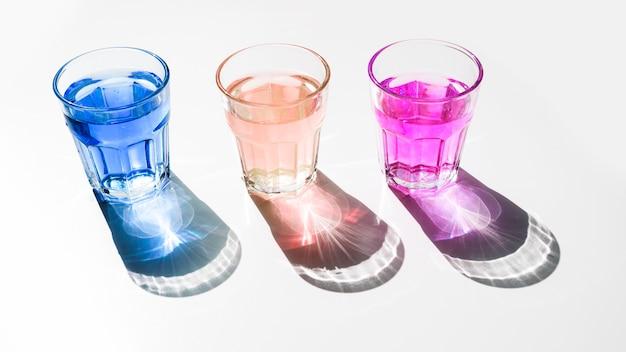 Azul; vidros líquidos cor-de-rosa e vermelhos com sombra escura brilhante no contexto branco