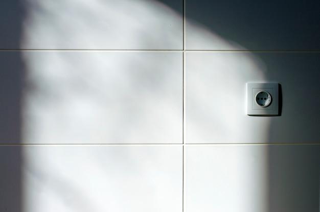 Azulejo branco iluminado pela luz da janela