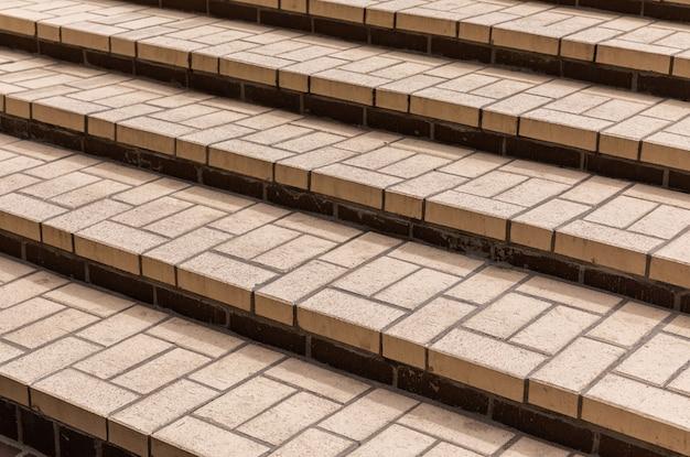 Azulejos bege de diferentes formas nos degraus da escada de concreto, vista diagonal