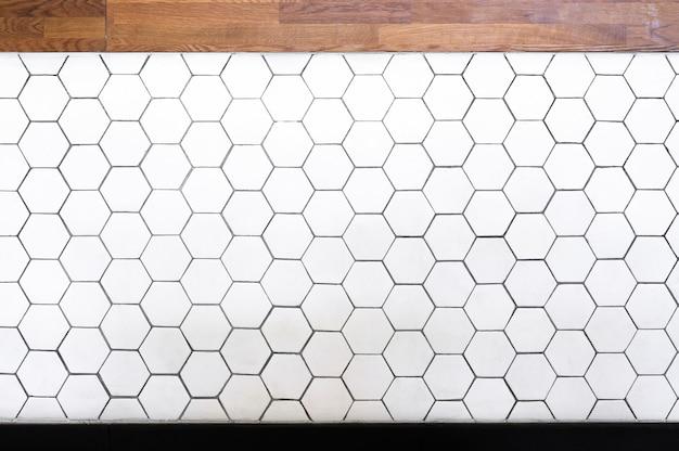 Azulejos hexagonais brancos simples e fundo de textura de madeira