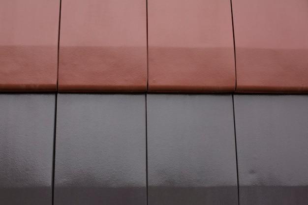 Azulejos pretos e vermelhos molhados após a chuva. foto de close