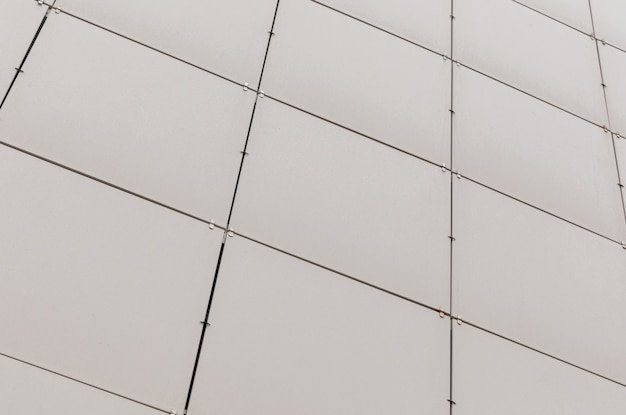 Azulejos quadrados bege sujos na superfície da parede, vista diagonal.