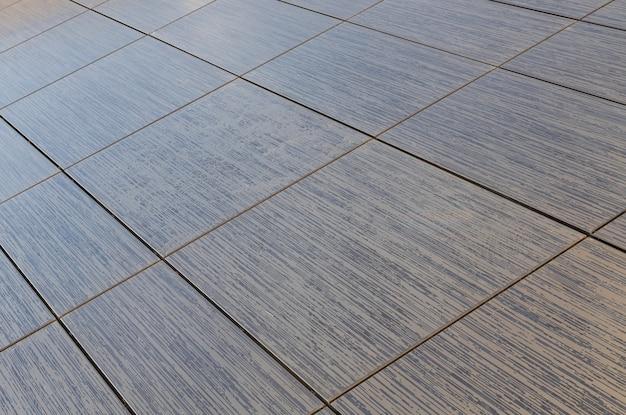 Azulejos quadrados marrons com padrões de listras pequenas em tamanhos diferentes para design de interiores