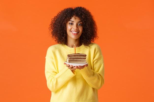 B-dia afro-americana sonhadora de retrato da cintura para cima com corte de cabelo afro, segurando o prato com bolo de aniversário e uma vela acesa, soprando para fazer um desejo, sorrindo feliz, comemorando sobre a parede laranja.