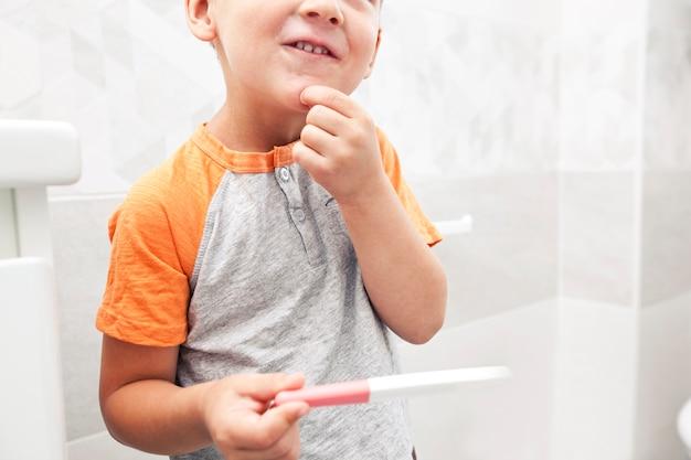 Ba criança encontrou o teste de gravidez positivo e está olhando e não sabe o que é.