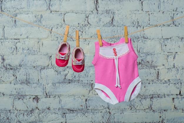 Babador de corpo rosa infantil e sapatos vermelhos secam em uma corda contra uma parede de tijolos brancos