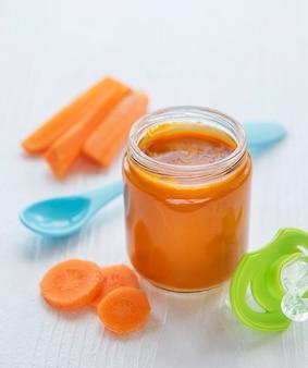 Baby cenoura amassada com colher em frasco de vidro, papinha
