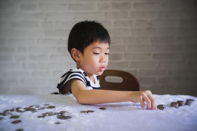 Baby moneybox colocar uma moeda em um cofrinho - garoto economizando dinheiro para o futuro conceito