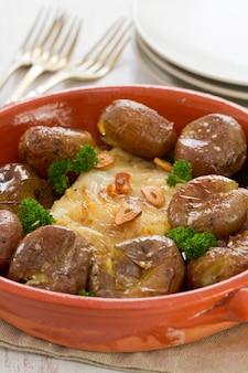 Bacalhau com batata no prato de cerâmico em madeira branco