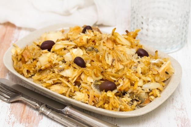 Bacalhau com batatas fritas e azeitonas no prato na superfície branca