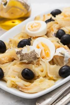 Bacalhau com cebola, azeitonas, ovos e azeite na travessa de cerâmica