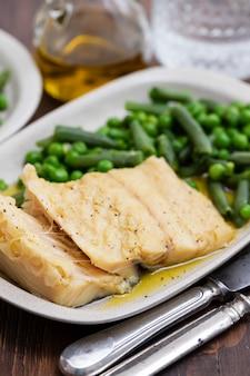 Bacalhau com feijão verde e ervilhas no prato