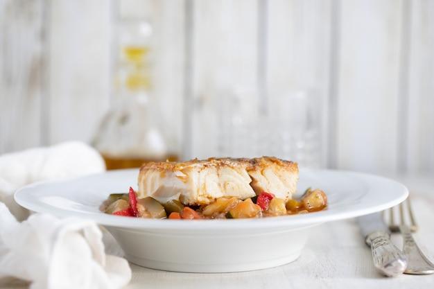 Bacalhau com legumes em prato branco