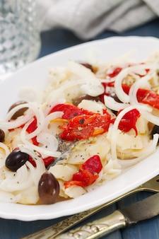 Bacalhau com pimenta vermelha e azeitonas em prato branco