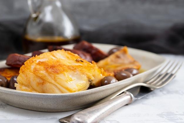 Bacalhau frito com azeitonas e batata doce no prato