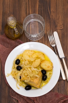 Bacalhau frito com cebola e batata no prato branco