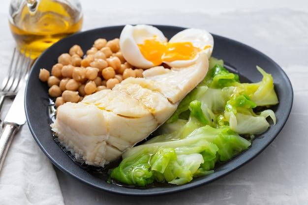 Bacalhau frito com grão de bico, ovo cozido e repolho em prato escuro