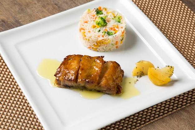 Bacalhau grelhado com arroz colorido.